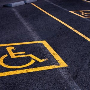Yellow signs of parking areas reserved for disabled people.