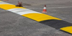 Just painted stripes on a speed bump for slowing traffic near school. Freshly painted speed bump. Selective focus.